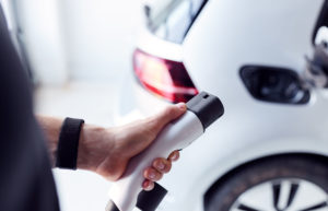 Close Up Of Hand Attaching Power Cable To Environmentally Friendly Zero Emission Electric Car